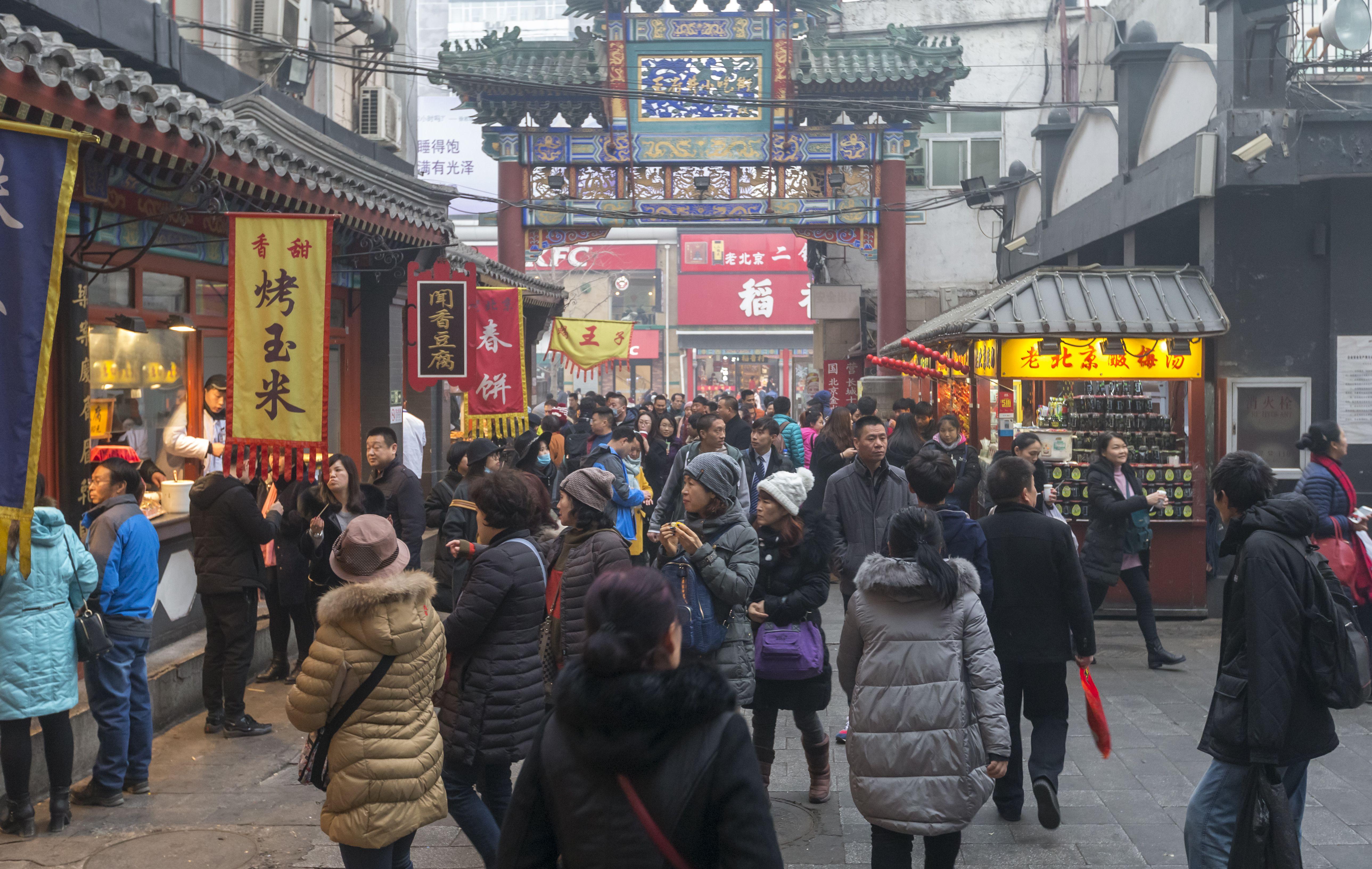 Pedestrians on Wangfujing Street, a shopping and snacking street in Beijing