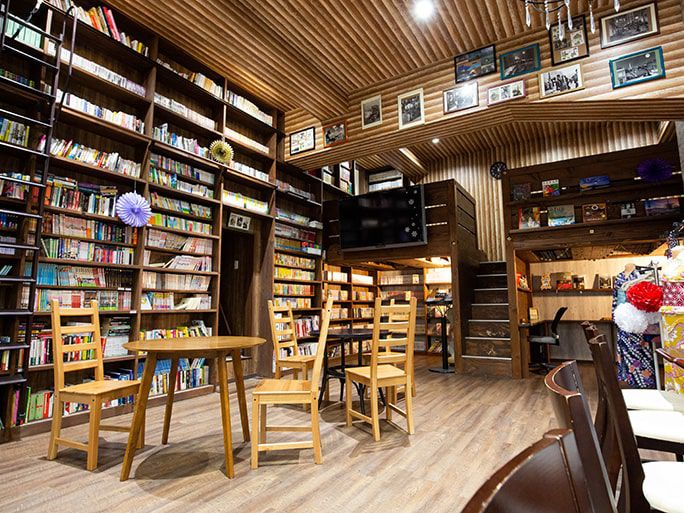 high ceilinged room with a wall of bookshelves, wooden furnitures and a small lofted area toward the back wall