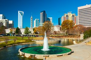 Downtown Charlotte skyscrapers in the background with a park (Marshall Park), fountain and waterway in the foreground