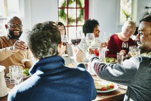 Smiling group of friends toasting during holiday meal together