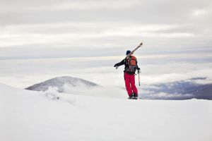 A skier stands on a ridge with his skies slung over his shoulder