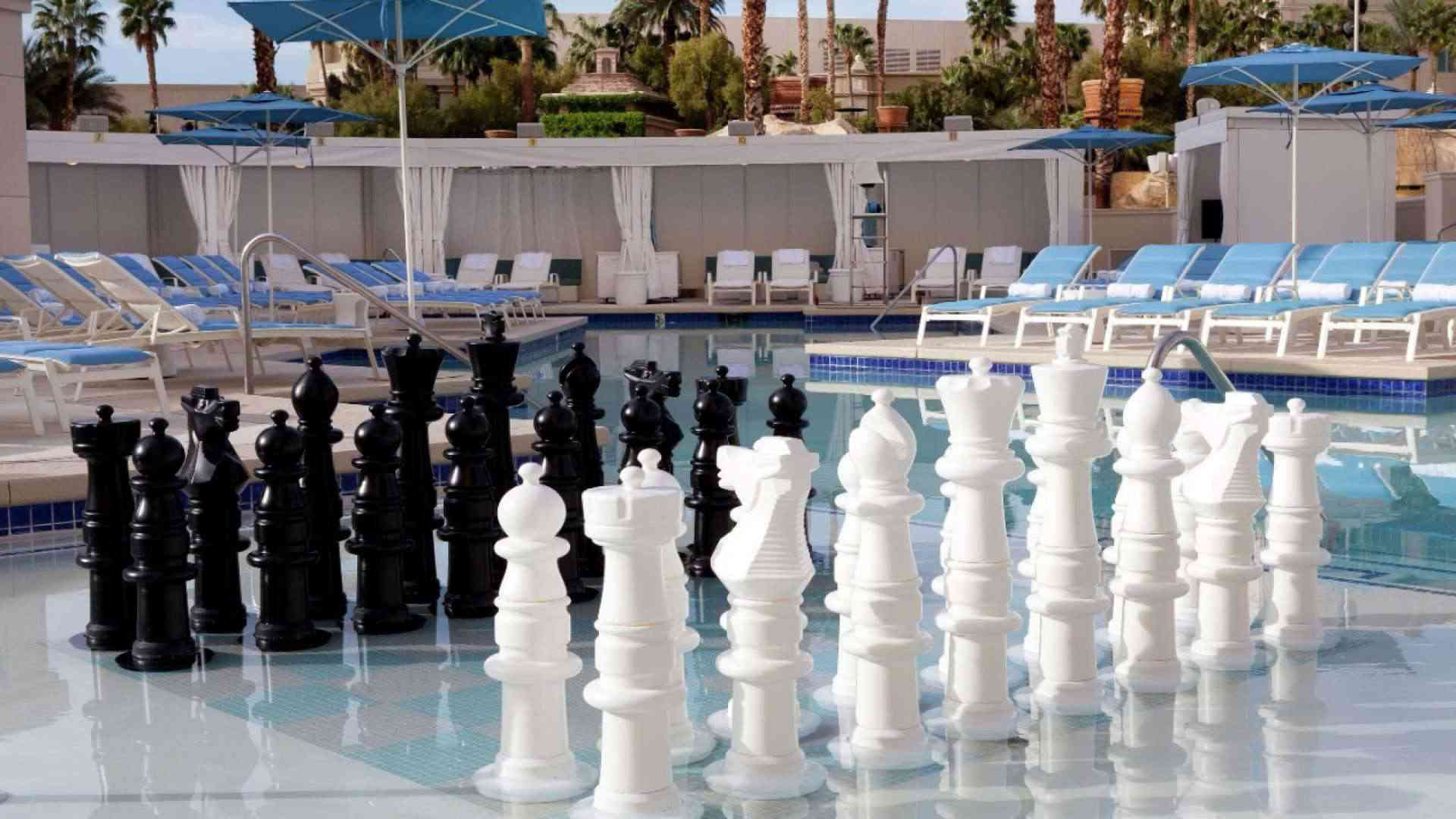 Oversized chess pieces partially submerged in an outdoor resort pool