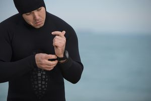 Diver man putting on waterproof watch.