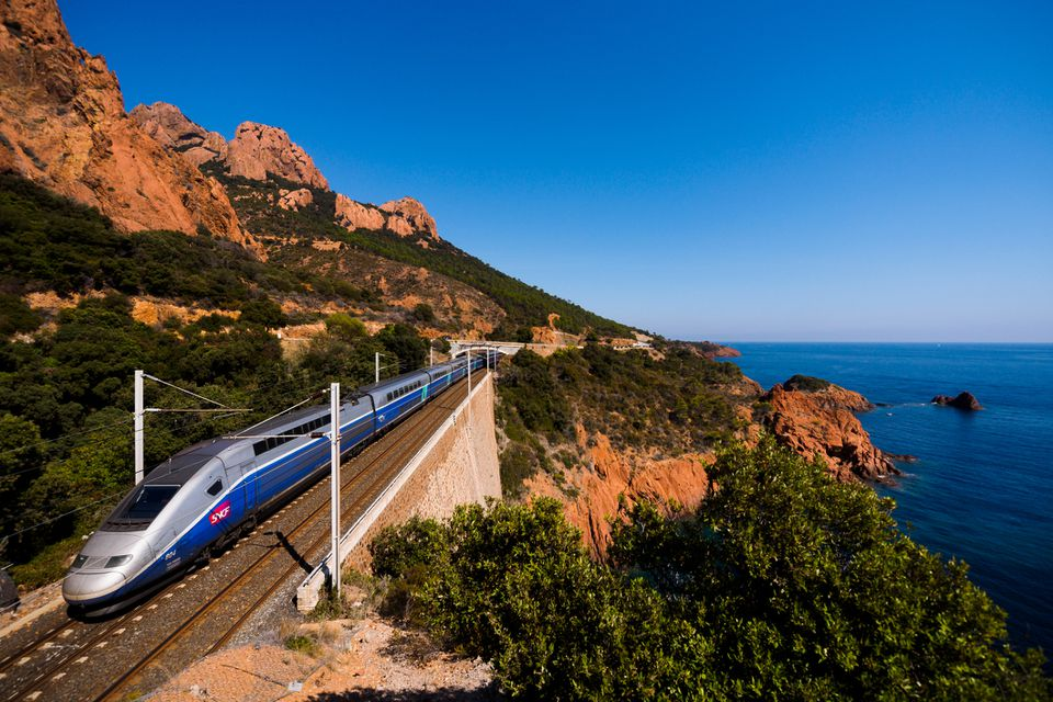 A french high speed train TGV running over a viaduct alongside mediterranean coast.