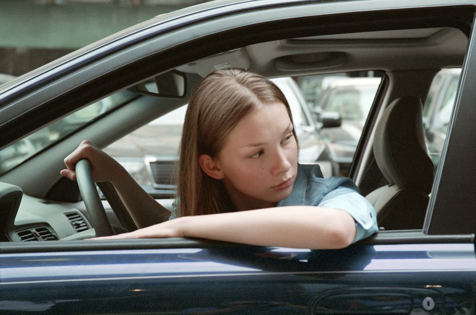 Young woman in traffic backing up car, close-up