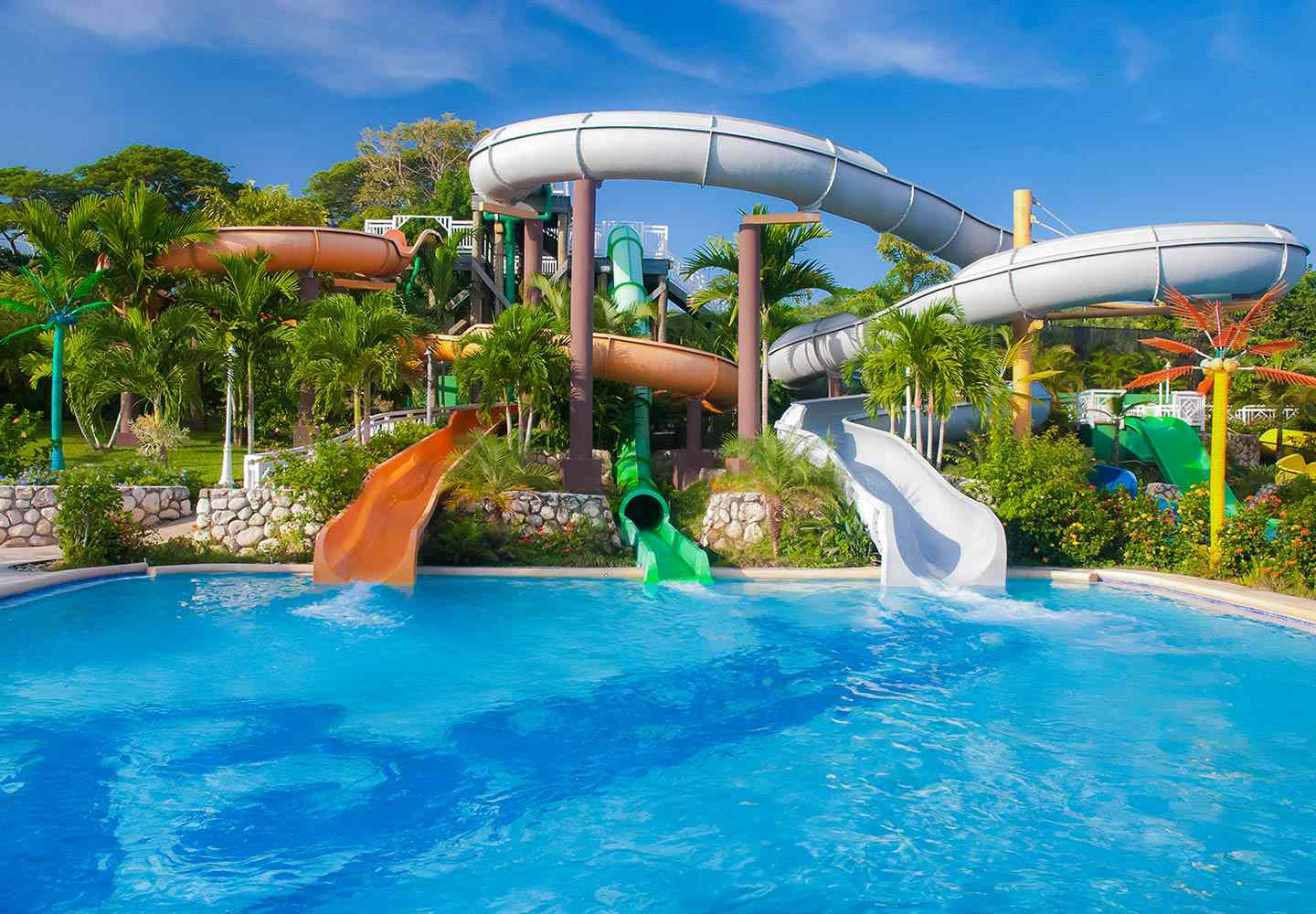 Three waterslides emptying into a pool