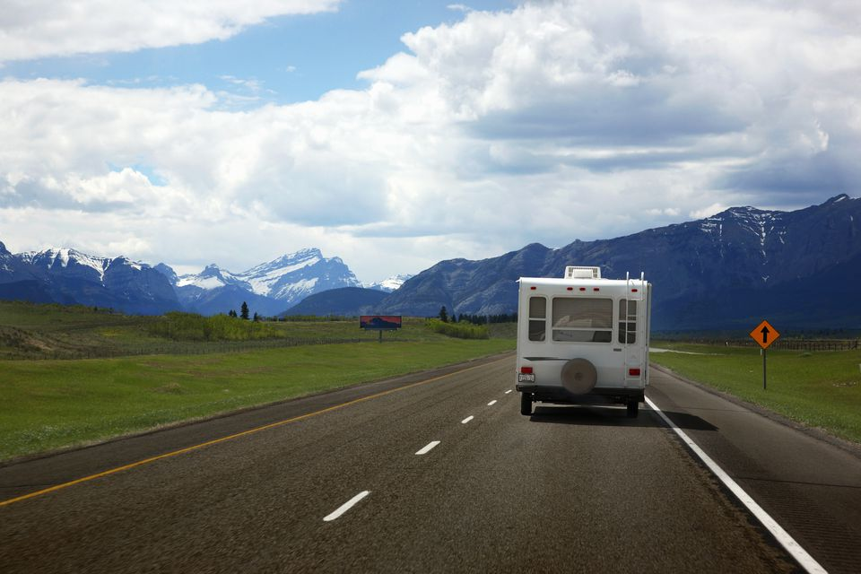 an RV driving on a highway toward mountains
