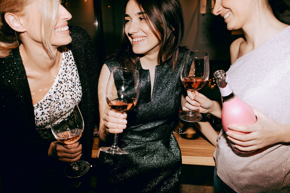 Women sharing a bottle of wine during girls' night out.