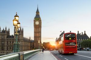 A picture of the Big Ben clock tower with a double decker bus in the foreground