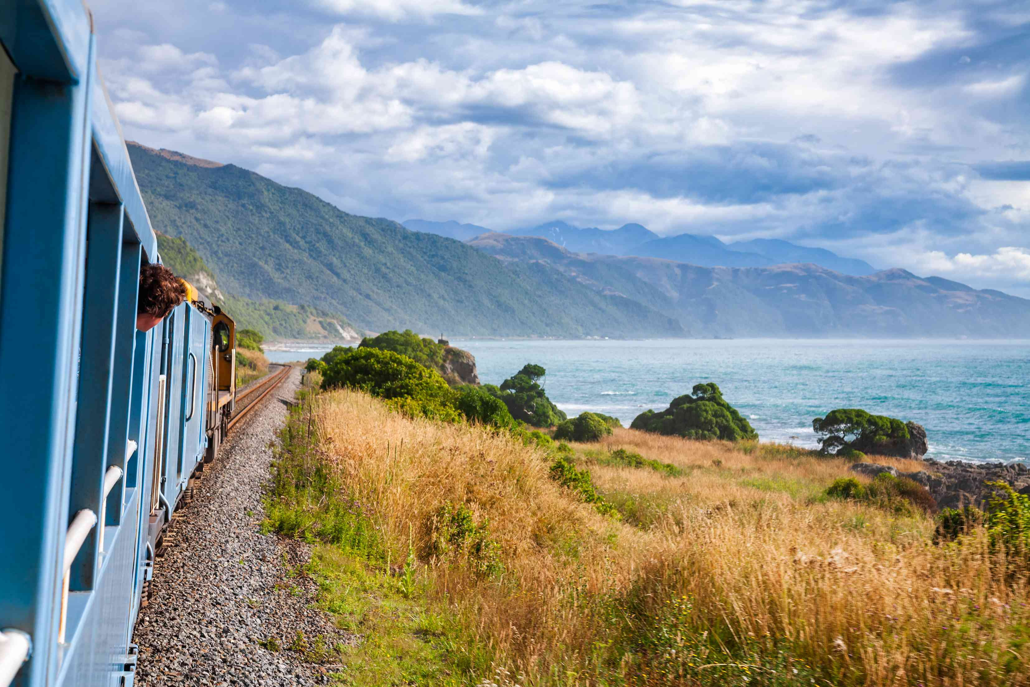 blue train traveling along coast with blue sea and cliffs