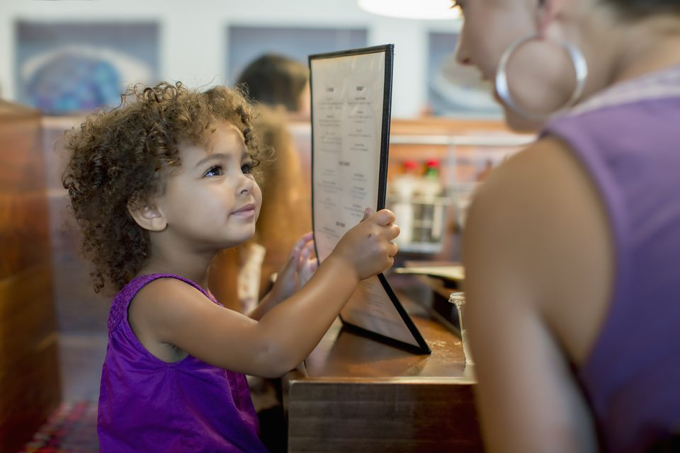 kid looking at restaurant menu