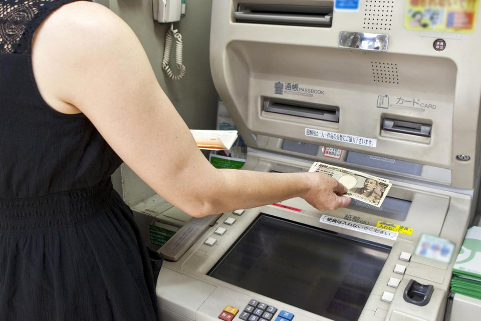 Woman withdraws cash from ATM machine