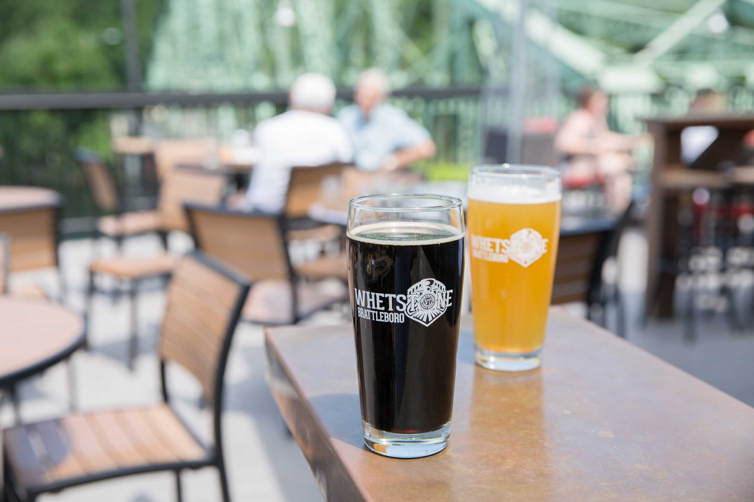 Two glasses of beer, one dark one light, on an outdoor patio at Whetstone Station Restaurant and Brewery Brattleboro Vermont