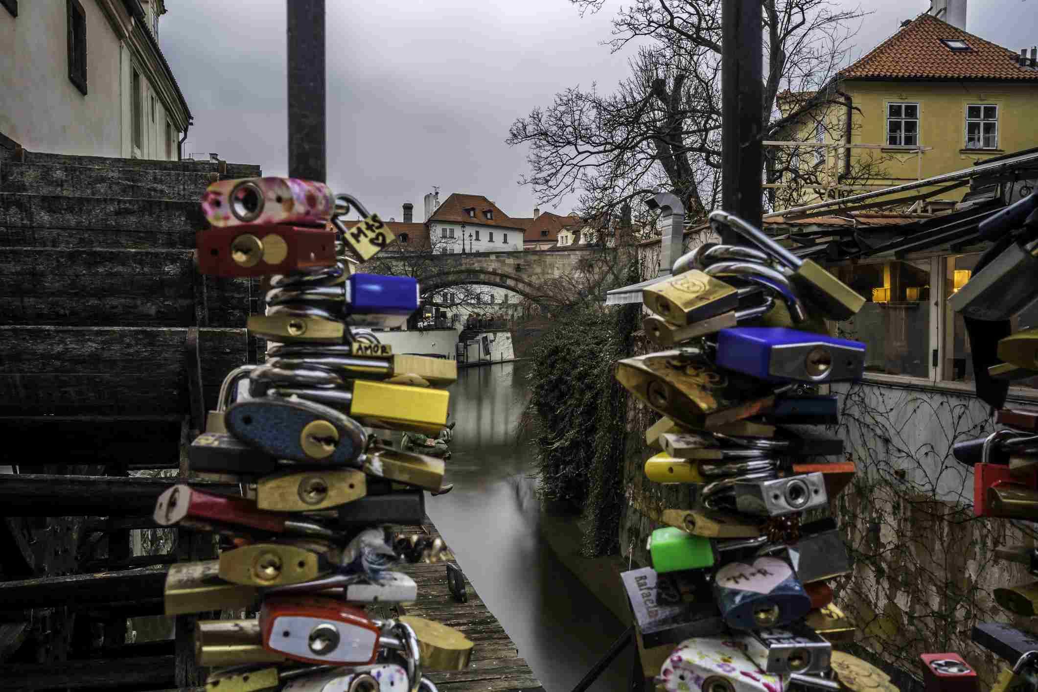 Love locks on a fence by old water mill on Kampa Island in Prague, Czech Republic.