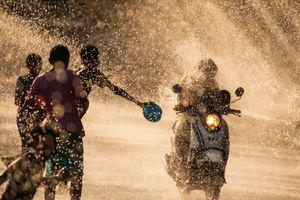People splashing a motorbike driver during Songkran celebrations in Thailand