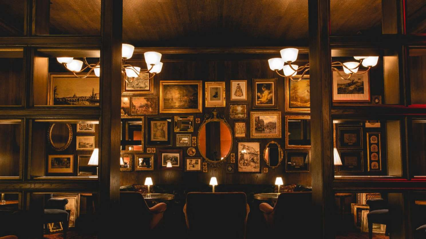 dimly lit restaurant with vintage framed pictures on a wall