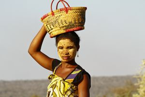 Portrait of a Malagasy woman in a traditional face mask holding a basket on her head
