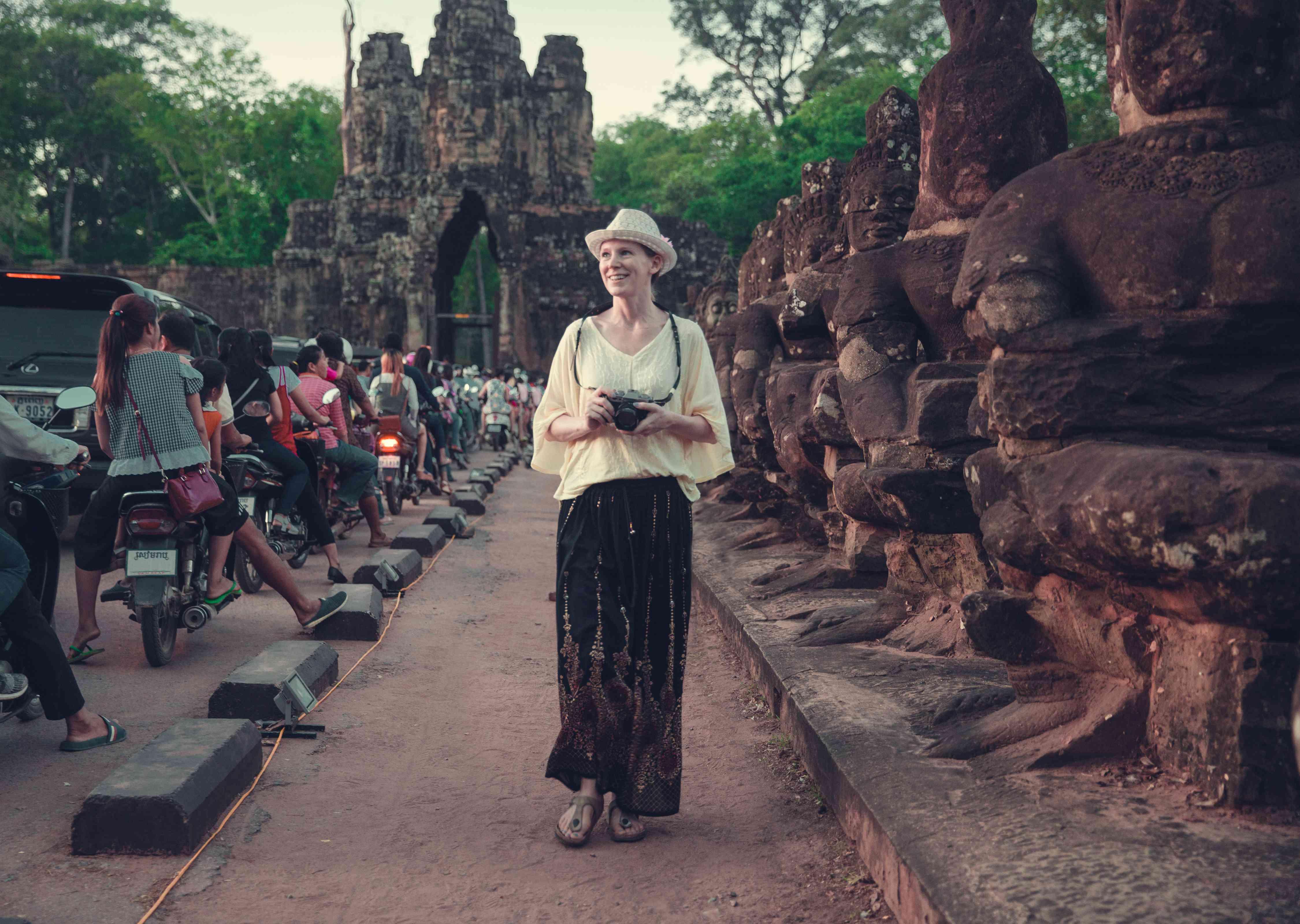 A female traveler walks a busy street in Cambodia