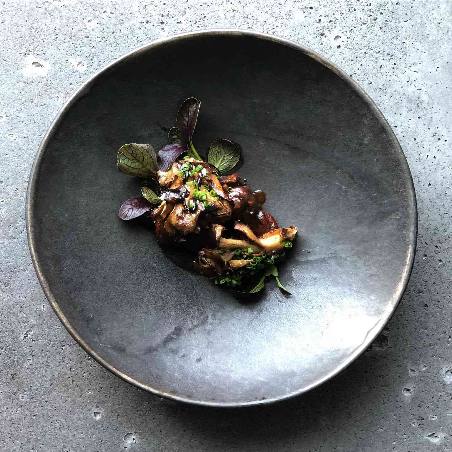 small portion of a mushroom and greens dish on a dark plate