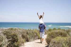 A picture of a daughter on her fathers shoulders walking down a path to the beach