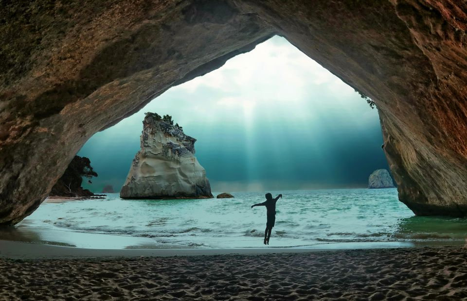 A silhouetted visitor jumps while throwing a rock into the water at Cathedral Cove, New Zealand