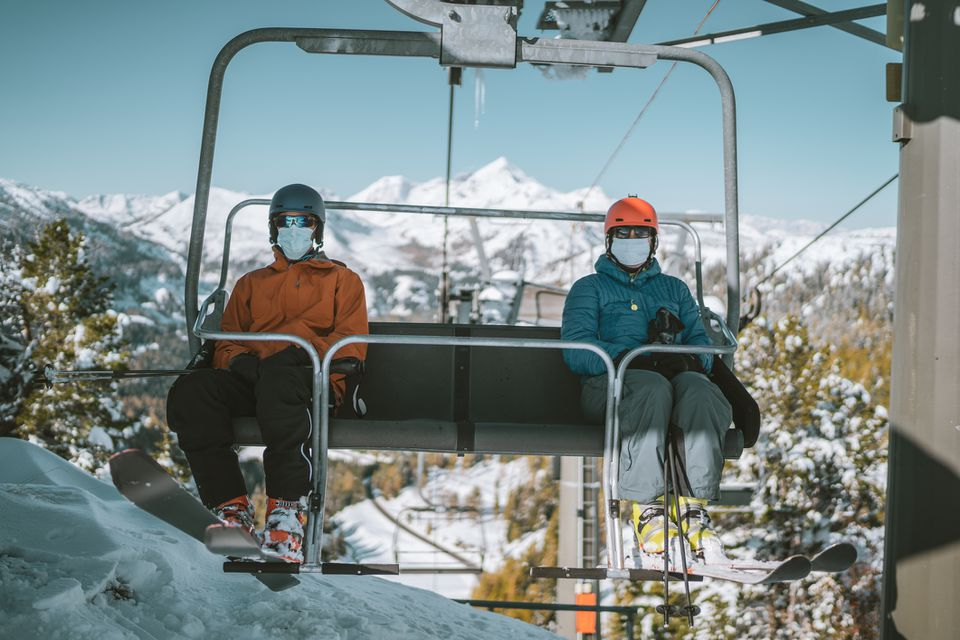 two skiers with mouth nose mask on chair lift