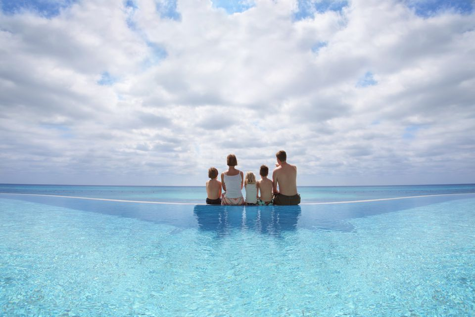 Family sitting on the edge of an infinity pool looking at at the Caribbean sea