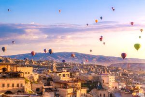 hot air balloons over buildings in Turkey, photographed at sunset