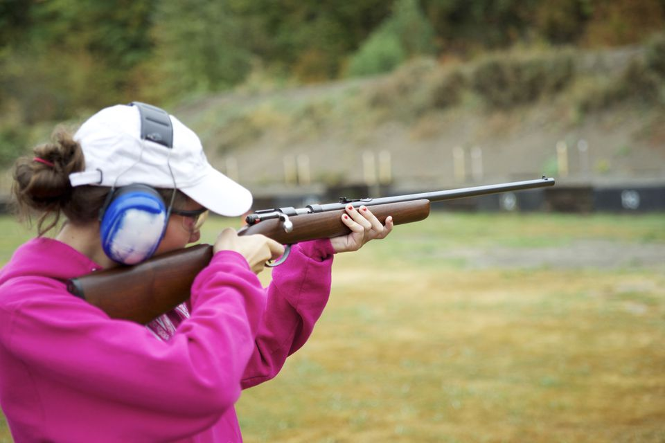 Teenage girl shooting bolt action rifle on rifle range.