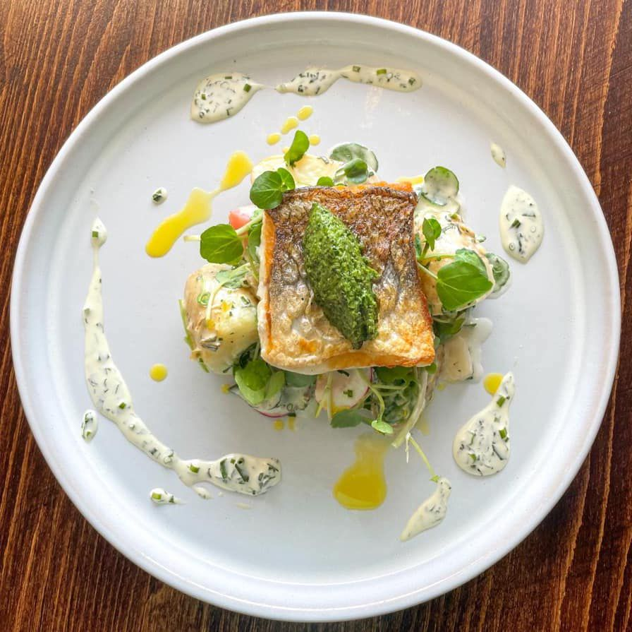 grilled fish with pesto, salad, and white dressing on a white plate