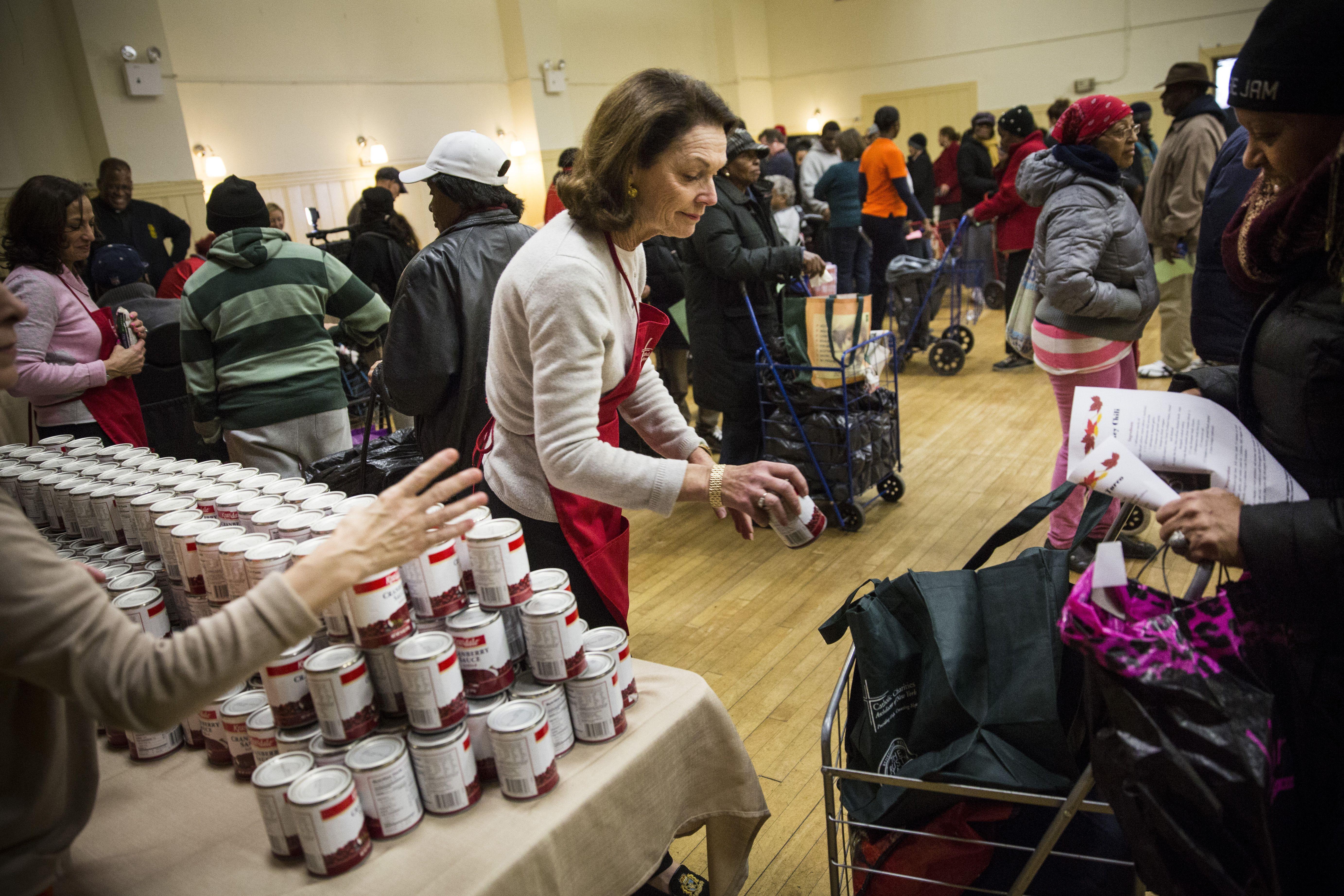 Caridades Católicas voluntarios manos productos enlatados durante Acción de Gracias