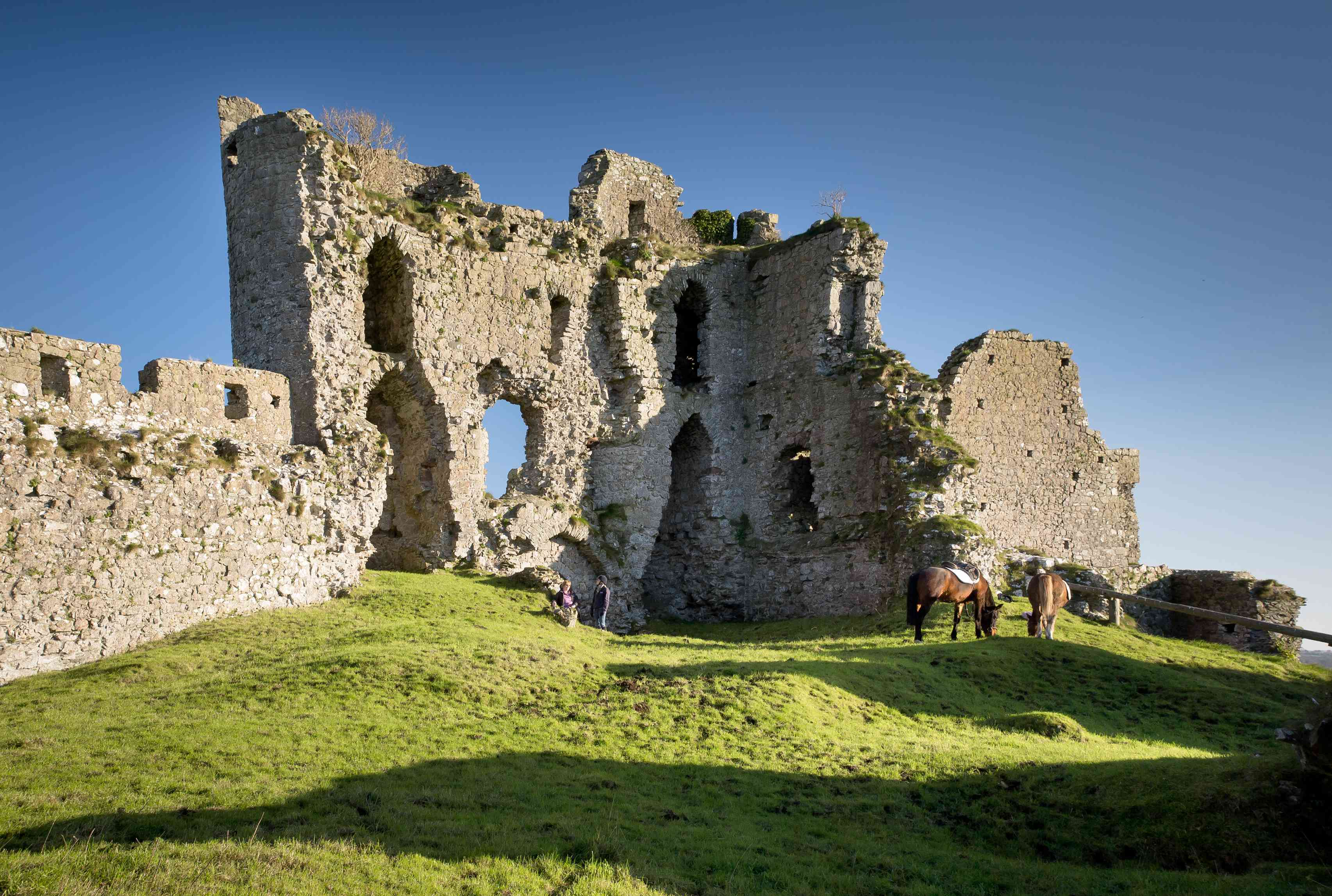 The ruins of Castle Roche in Dundalk with two horses grazing nearby and two people standing next to the ruins