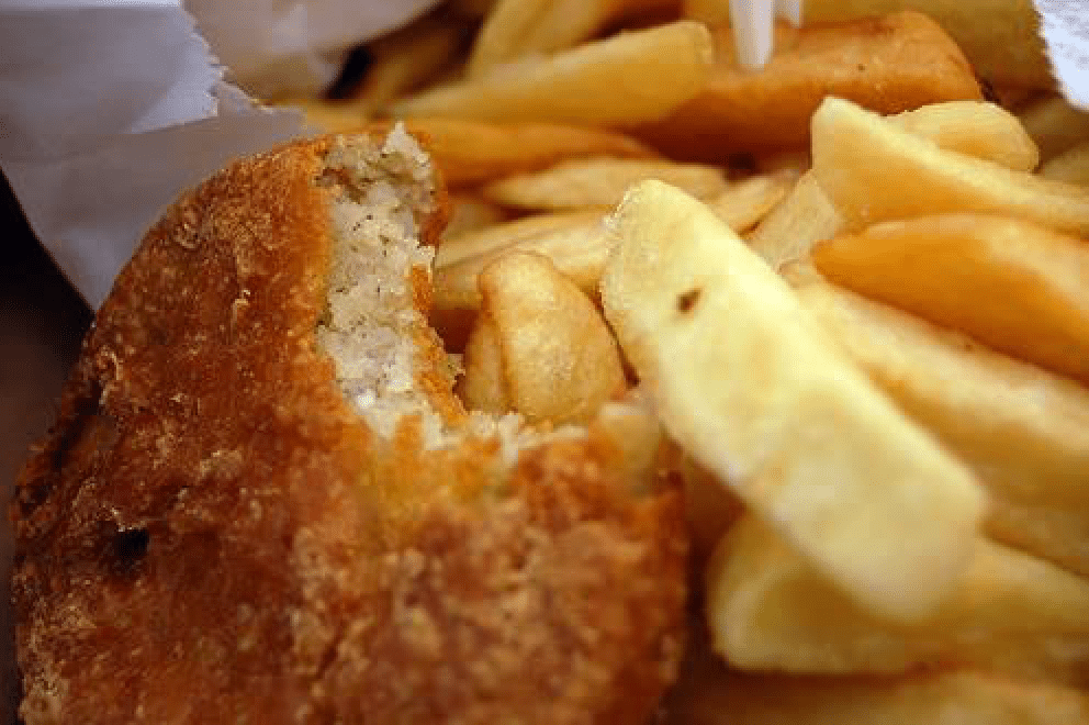 Close up of a pasty with a bite taken out of it and some french fries