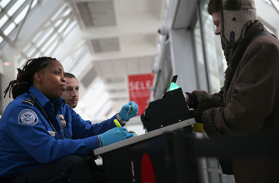 A TSA agent checks a traveler's identification at a special TSA Pre-check lane at Terminal C of the LaGuardia Airport