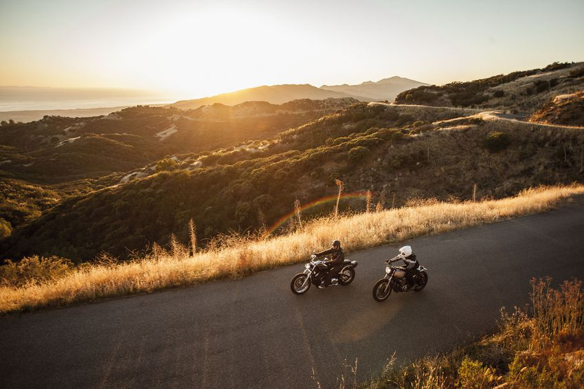 Two friends riding motorcycles together on country roads