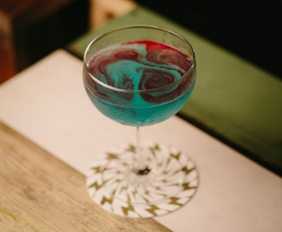 Blue and red swirled drink on a light brown, white and green table