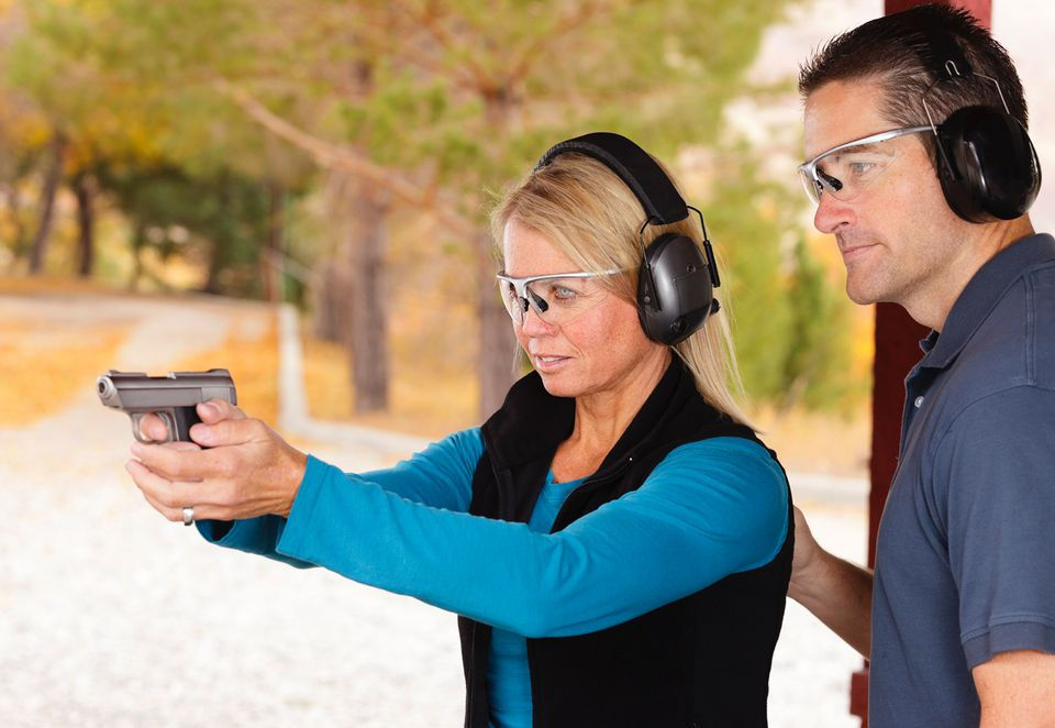 A woman and man shooting at a gun range