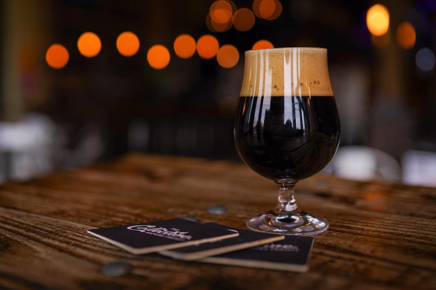 Stout from The Collective Brewing Project on a wooden table with three coasters on it