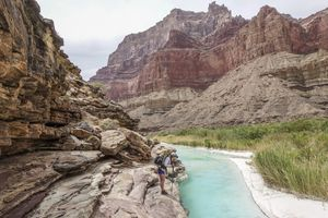 Landscape with young woman standing on rock formation and contemplatingturquoise water of Little Colorado River near its confluence with Colorado deep down in Grand Canyon, Grand Canyon, Arizona, USA