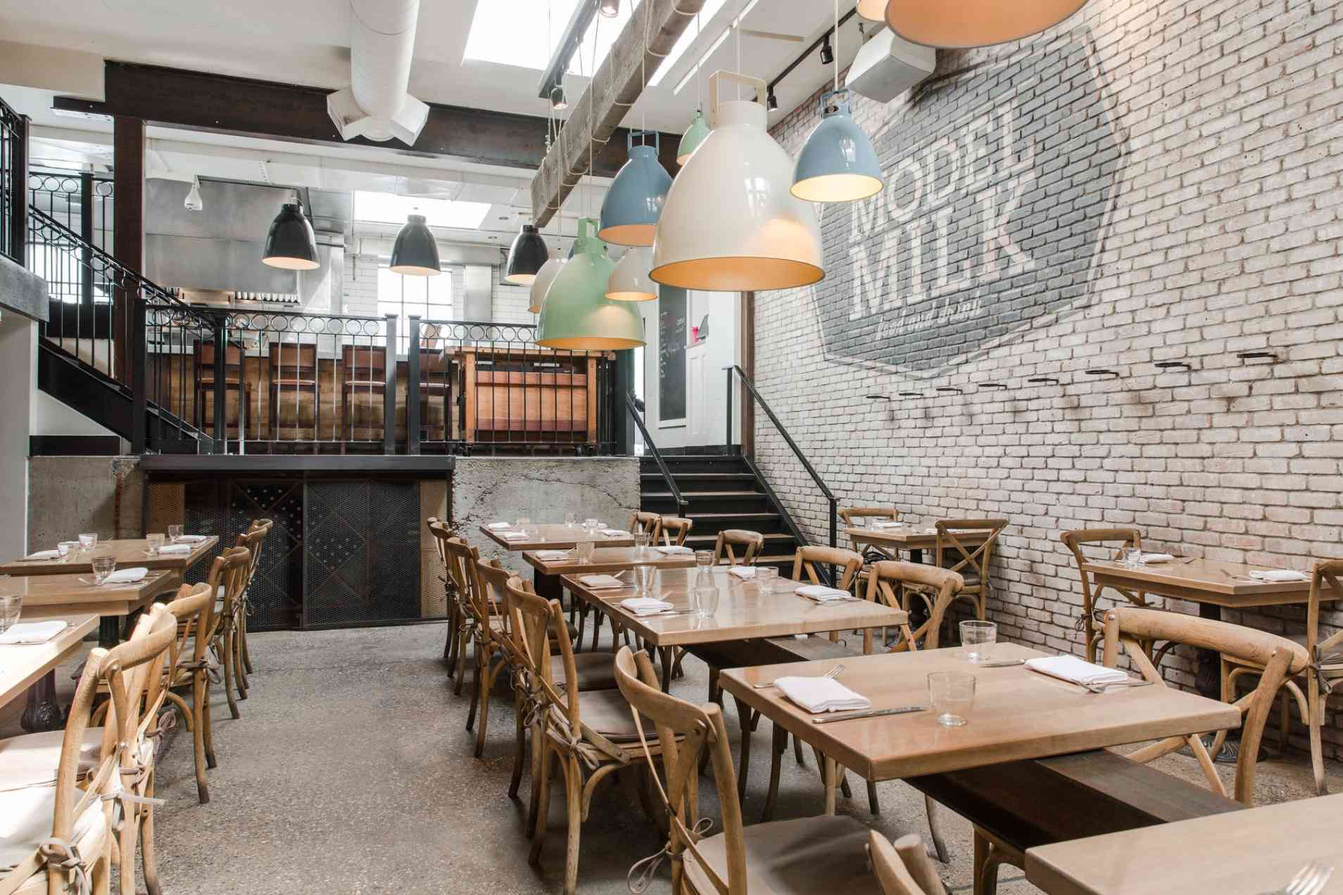restuarant dining room with off-white brick walls, light wooden tables and pastel painted light fixtures