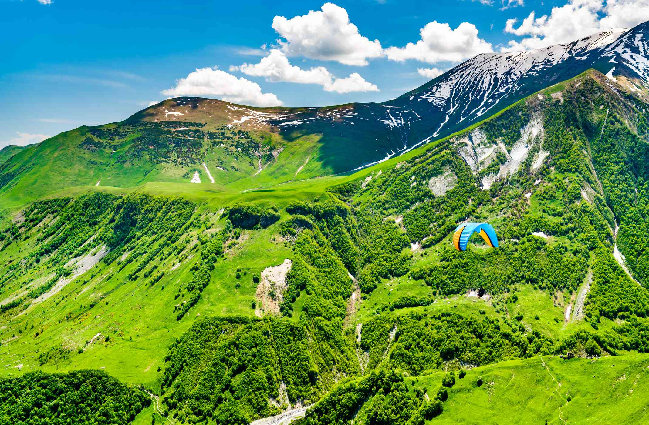 green mountains with blue paraglider in mid ground
