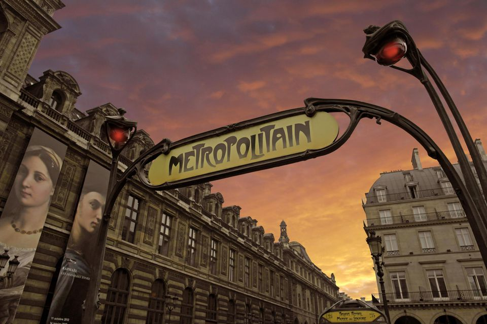 Paris metro sign in front of the Louvre Museum