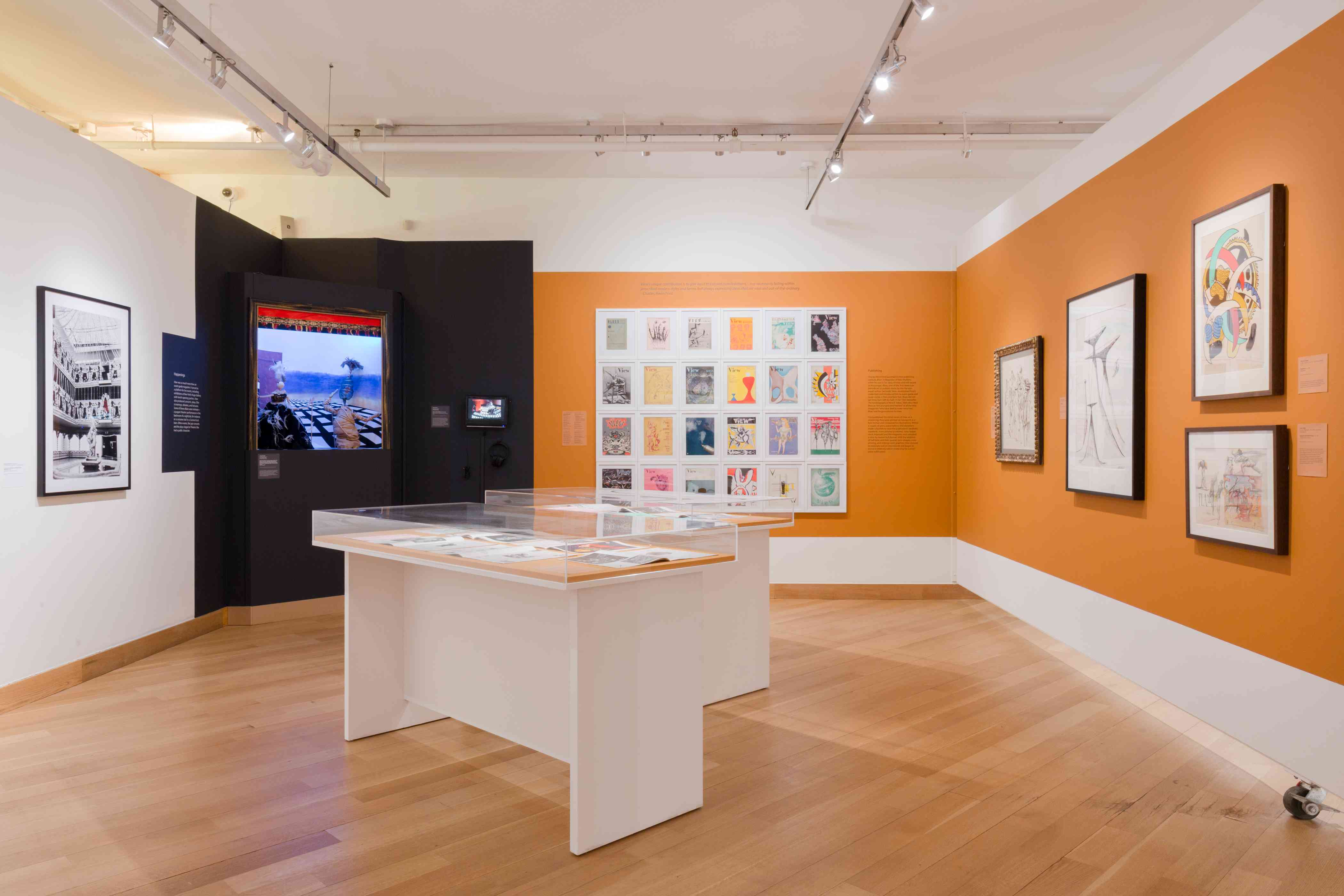 Art gallery with orange walls and display cases in the middle of the room