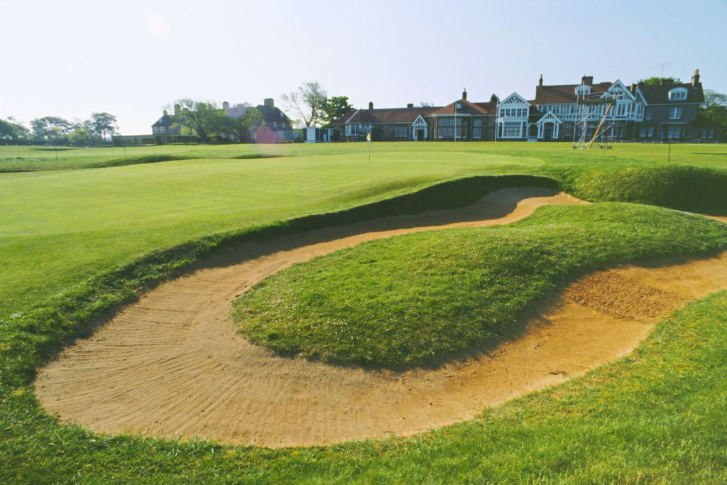 sand trap on a golf course with a large house in the background