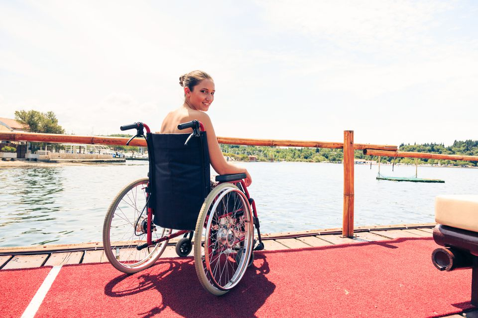 Young disabled woman sitting in wheelchair having a good time by the sea.