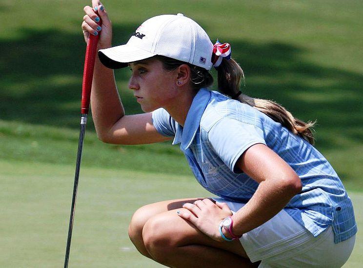 una joven que mira su pelota de golf en el green