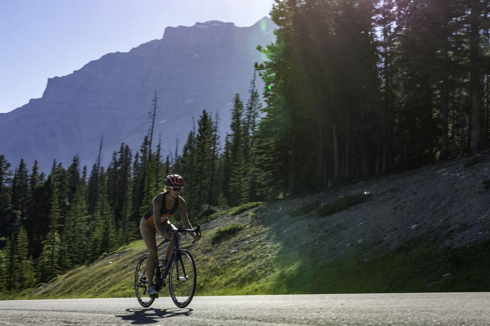 Triathlete trains on mountain road, sunrise