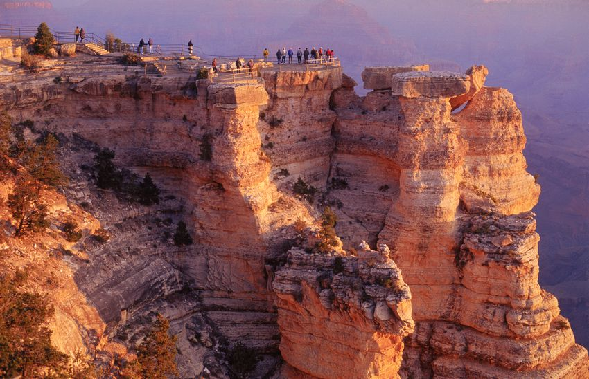 Group of tourists standing on cliffs of Grand Canyon