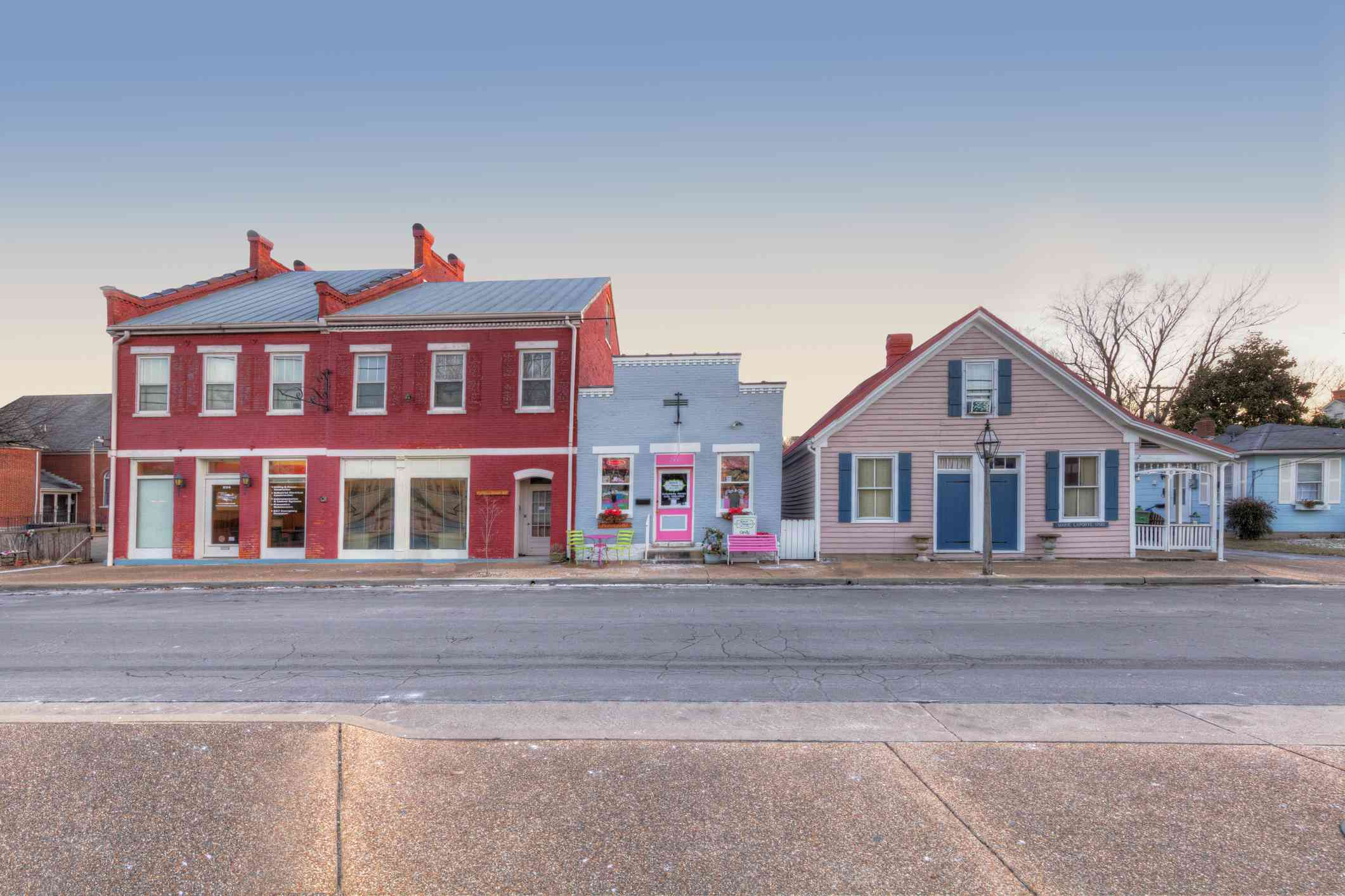 A cluster of three colorful old buildings on photographed from across an empty street