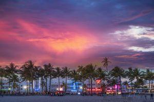 Beachfront buildings under sunset sky